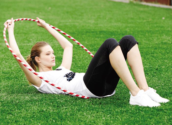 • En este ejercicio el hula sirve de contención para el trabajo abdominal sobre el suelo.   • Acostada con la espalda recta y las piernas semiflectadas, el aro se acomoda justo detrás del trasero en dirección a la cabeza con los brazos afirmándolo con fuerza para ejecutar un total de 15 abdominales cortos.