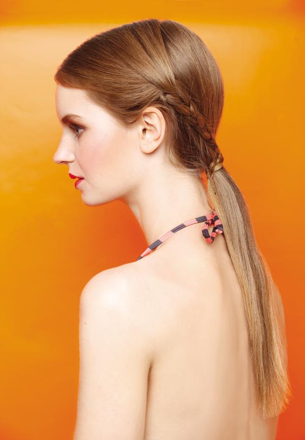 3. Amarre las trenzas hacia atrás y crúcelas. Para terminar junte con un elástico todo el cabello en una cola baja y cúbralo con los mechones trenzados.