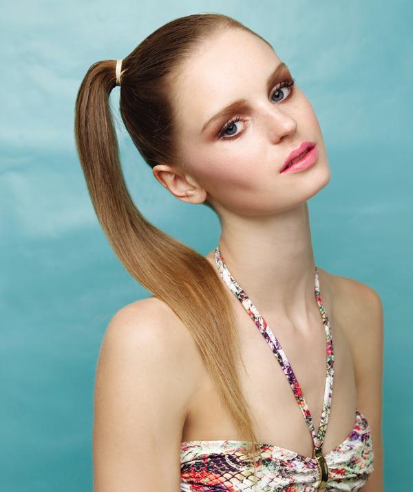 1. Peine todo el pelo y haga una cola firme inclinada hacia un extremo de la cabeza. Este look funciona mejor con cabellos lisos, pero también se puede replicar en melenas onduladas. En ese caso el resultado es más desordenado y casual.