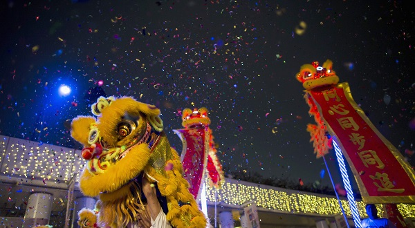 Lion dance troupes perform during a Chinese New Year evening parade at Hong Kong's Tsim Sha Tsui shopping district