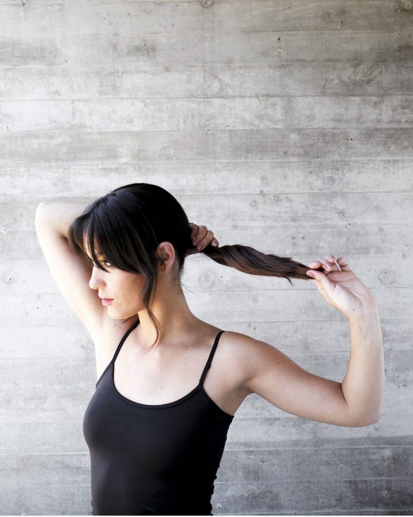 2) Haz una cola baja, dejando los mechones ondulados adelante. Separa el pelo a los costados de la cabeza para lograr un look relajado. Aplica fijador si es necesario.