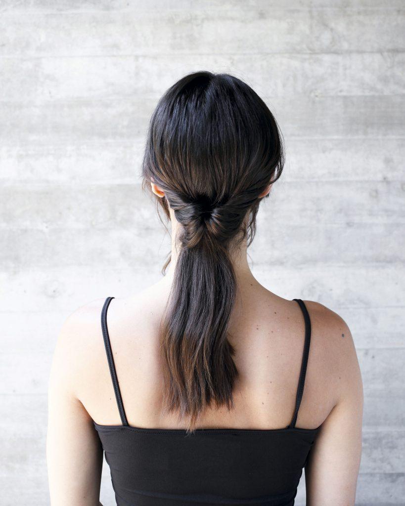 3) Separa el colet de la nuca y deja un espacio al medio. Introduce por arriba el pelo de la cola y tira hacia abajo, dándola vuelta lograrás un efecto elegante ¡y superfácil!