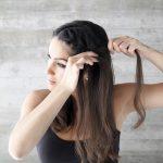 2) Selecciona pelo para hacer una trenza María desde arriba de la frente hasta la oreja. Afírmala con un elástico.